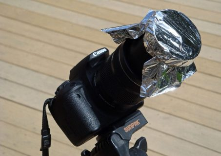 An easy solar filter: Baader AstroSolar Safety Film OD 5.0 over a camera lens and held in place with elastic bands (Photo by Paul Deans/TQ).
