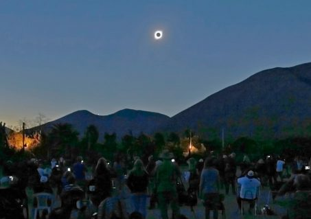 Special eclipse glasses provide a safe solar view. Inset: The view through eclipse glasses.